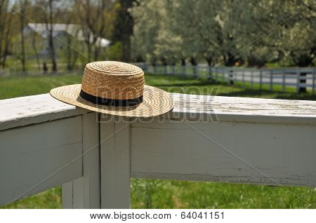 Amish Straw Hat On A White Fence