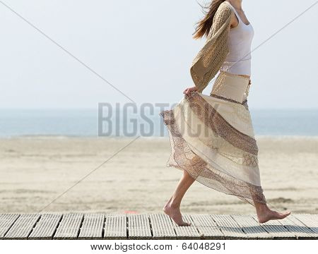 Female Walking At The Beach Barefoot With Dress