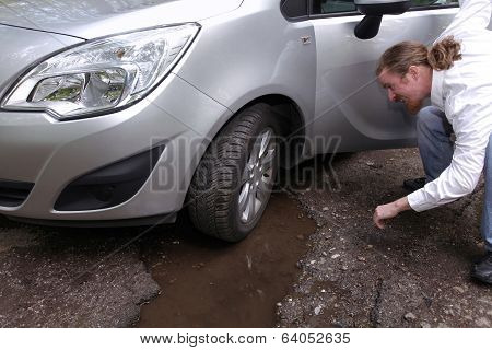 Upset Driver Man In Front Of Automobile Watching Damaged Car Of Road Full Of Cracked Potholes In Pav
