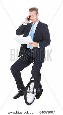 Businessman Sitting On Unicycle Talking On Cellphone