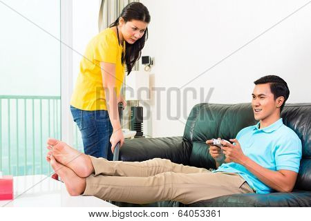 Young Asian handsome couple having relationship difficulties with household tasks like vacuum and playing games on couch