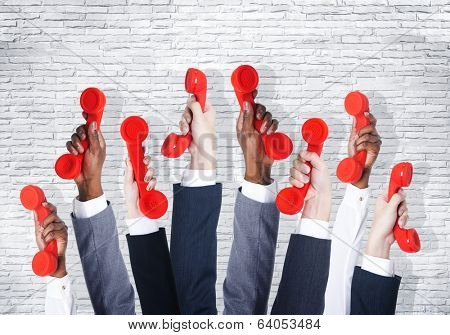 Business people holding red phone.