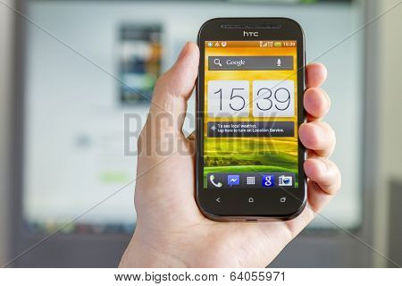 Closeup Of Man's Hand Holding A Smartphone In Office