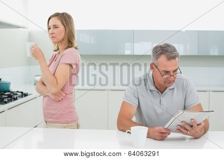 Displeased woman drinking coffee while man reading newspaper in the kitchen at home