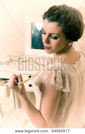 Young vintage 1920s woman choosing jewelry in her boudoir