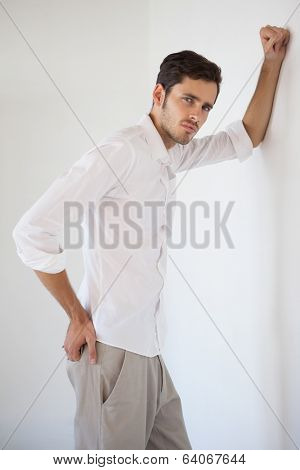 Casual businessman leaning against the wall in his office