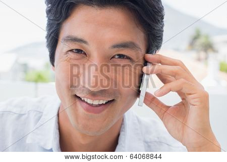 Smiling man on phone call outside on a balcony