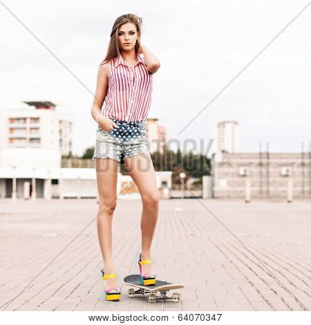 Beautiful Lady In Short Jeans Shorts Stands On Skateboard