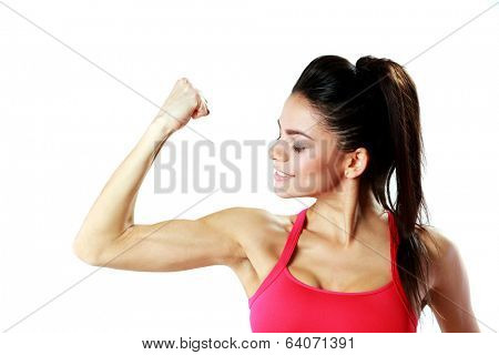 Young sport woman looking at her biceps over white background