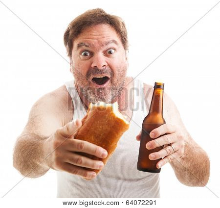 Scruffy man watching a sporting event, holding a sub sandwich and a beer.  Isolated on white.