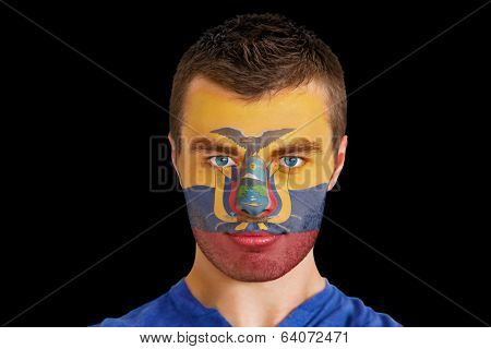 Composite image of serious young ecuador fan with facepaint against black