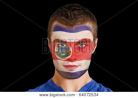Composite image of serious young costa rica fan with facepaint against black