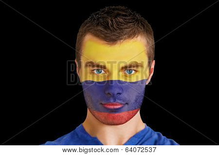 Composite image of serious young colombia fan with facepaint against black