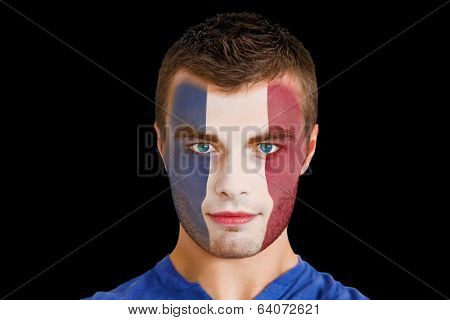 Composite image of serious young france fan with facepaint against black