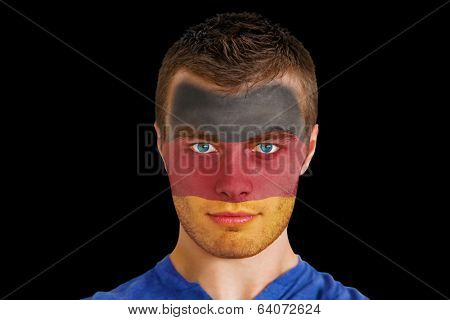 Composite image of serious young germany fan with facepaint against black