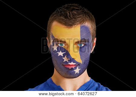 Composite image of serious young bosnian fan with facepaint against black