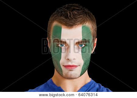 Composite image of serious young nigeria fan with facepaint against black