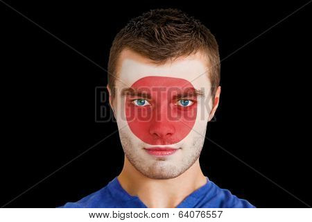 Composite image of serious young japan fan with facepaint against black