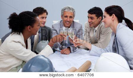 Equipo de Architectutal feliz teniendo una celebración con Champagne