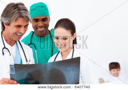 Medical Team Examining An X-ray And A Little Boy In Bed