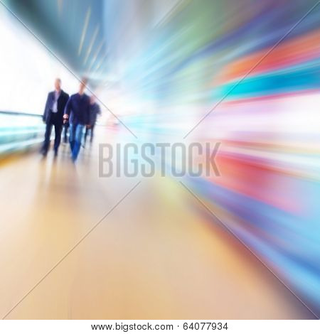 People in motion blur walking in the office corridor.