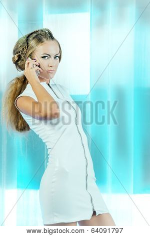 Futuristic young woman in white latex dress calling by cell phone. Sci-fi style.