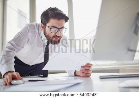 Puzzled businessman looking at paper in his hand by computer monitor in office