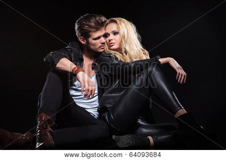 handsome young woman sitting on the floor with her boyfriend and looking at him over her shoulder . on black background