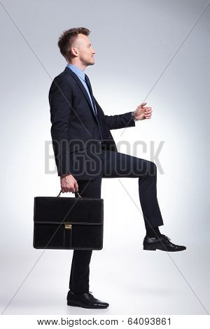side view of a business man stepping on some imaginary steps with a briefcase in his hand. on a gray background
