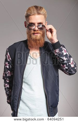 casual young man with a long red beard looking into the camera over his sunglasses while holding a hand in his pocket. on gray studio background