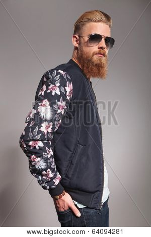 side view portrait of a casual young man with a long red beard holding his hands in his back pockets and looking into the camera. on gray studio background