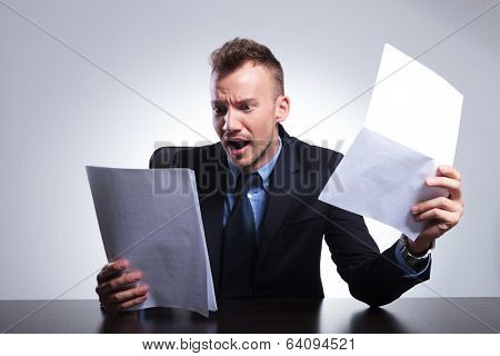young business man in shock after reading his bills. on a light gray studio backgroud