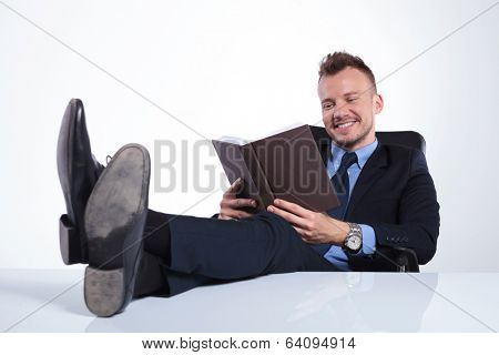 young business man reading a book with his feet on the desk and smiling. on a light studio background