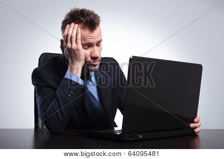 bored young business man falling asleep in front of his laptop. on a gray studio backgroud