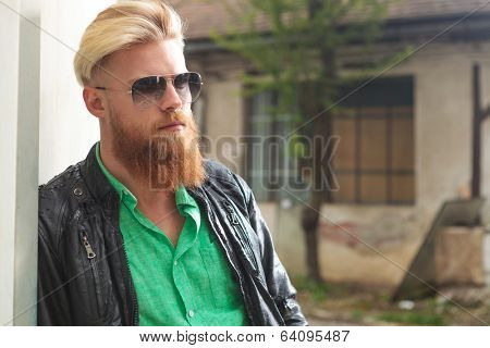 outdoor photo of a young casual redhead bearded man with sunglasses, looking away from the camera