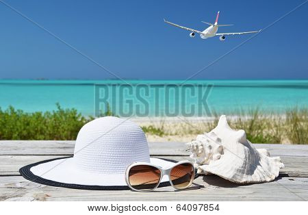 Sunglasses, hat and shell against ocean. Exuma, Bahamas