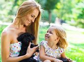 stock photo of puppies mother dog  - Cute little girl and her mother hugging dog puppies - JPG