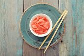foto of zingiber  - Pickled ginger with wooden chopsticks on plate top view - JPG