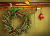 stock photo of christmas wreaths  - Old pair of skis hanging with wreath against green wood background - JPG