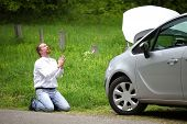foto of praying  - Funny driver praying a broken car by the road - JPG