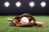 stock photo of baseball bat  - Baseball Glove With Baseball And Bat Lying On Green Grass - JPG