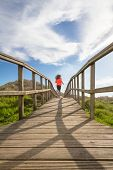foto of start over  - Back view of young girl running in training over wood boardwalk on a sunny day - JPG