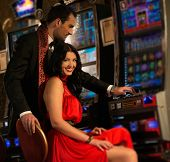 image of gambler  - Beautiful young couple near slot machine in a casino - JPG