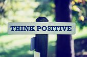 stock photo of think positive  - Retro  style image of a motivational message Think positive written on wooden signpost in wooodland - JPG