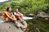 stock photo of hawaiian girl  - Hiking couple of hikers in outdoor activity wearing backpacks relaxing - JPG