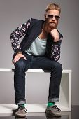 pic of thinker  - casual young man with a long red beard sitting like the thinker and looking into the camera - JPG
