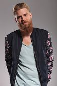 image of long beard  - casual young man with a long red beard looking into the camera with a smile on his face while holding hands in back pockets - JPG