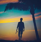 image of stroll  - Retro Vintage Filtered Photo Of A Man Strolling On A Beach In Hawaii With Palm Tree At Sunset - JPG