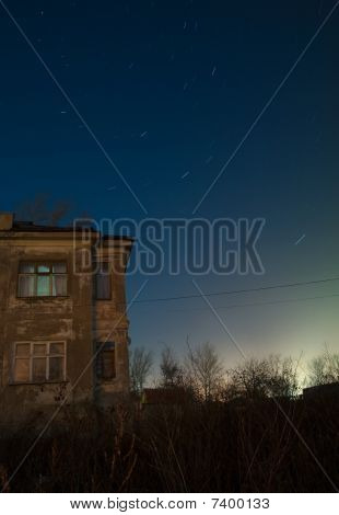 Star trails over old house