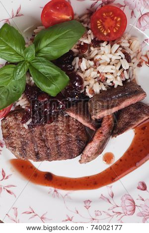 MedIum done grilled steak with cooked rice and cranberry sauce